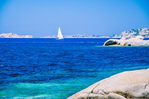 White sailboat, yacht between granite rocks in sea, amazing azure water, Sardinia, Italy