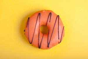 Orange donut with icing on a yellow background. Top view. Minimal concept