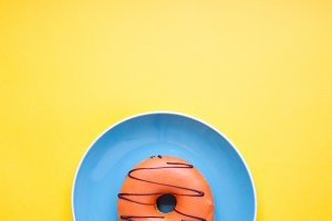 Blue plate with an orange donut in the glaze on a yellow background. Top view with copy space. Minimal concept