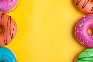 A set of sweet donuts on orange background. Top view with copy space