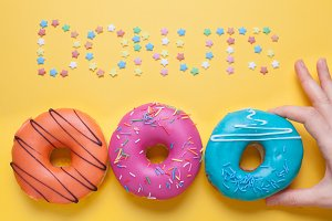 A female hand takes a blue donut in the glaze. Nearby lie pink and orange donuts. Top of the inscription donuts made of sugar stars