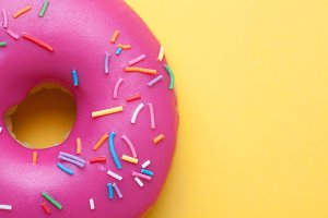 Raspberry donut with icing on a yellow background. Top view with copy space