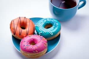 A cup of tea and a plate with donuts in a glaze on an white background