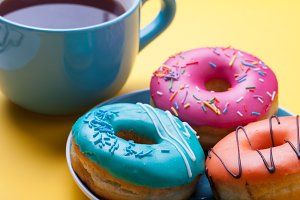 A cup of tea and a plate with donuts in a glaze on an orange background