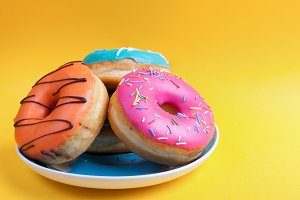 Plate set of donuts in the glaze on an orange background