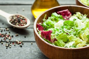 A dish of fresh salad frisse, Romano and radiccio with olive oil, salt and freshly ground percec in a wooden bowl