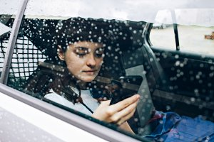 Woman waits for taxi in a car