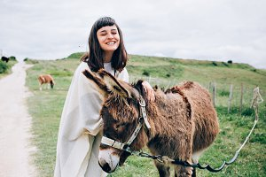 Woman pets cute donkey