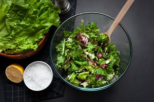 Fresh vegetarian salad mix in a clear glass bowl on a black background.