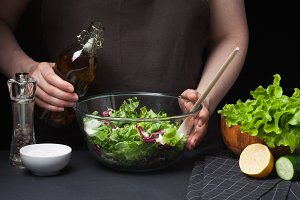 Woman chef in the kitchen preparing vegetable salad. Healthy Eating. Diet Concept. A Healthy Way Of Life. To Cook At Home. The girl is going to water the lettuce with olive oil on a dark background