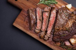Grilled ribeye steak of marble beef closeup with spices on a wooden Board. Juicy steak medium sliced and ready to eat. With copy space. Top view