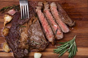 Grilled rib-eye steak of marble beef closeup with spices on a wooden Board. Juicy steak medium rare, sliced and ready to eat