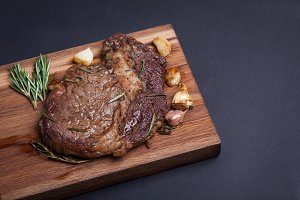 Grilled ribeye steak of marble beef with spices on wooden Board. With copy space