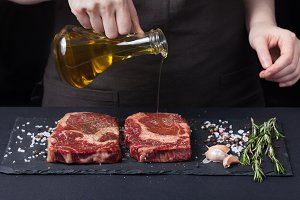Female chef pouring olive oil, two fresh raw steak ribeye beef on a dark background. Nearby is a mixture of peppers,sea salt, garlic and rosemary