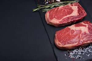 Two fresh raw marble meat, black Angus ribeye steak with spices on a dark stone background.