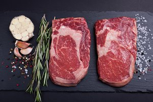 Two fresh raw marble meat, black Angus ribeye steak with spices on a dark stone background