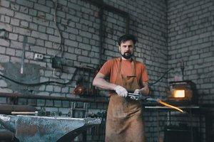 Blacksmith inspects the workpiece knife