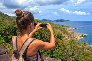 Woman taking photo of seaview with smartphone at mountain