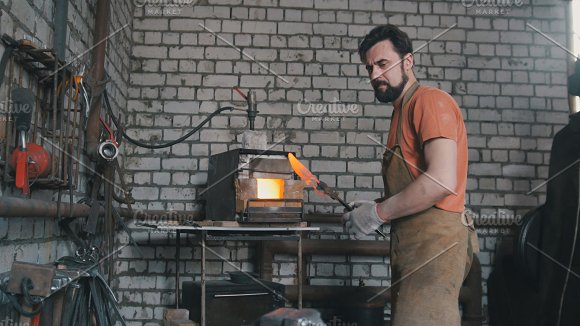 Young muscular man working on a blacksmith with metal