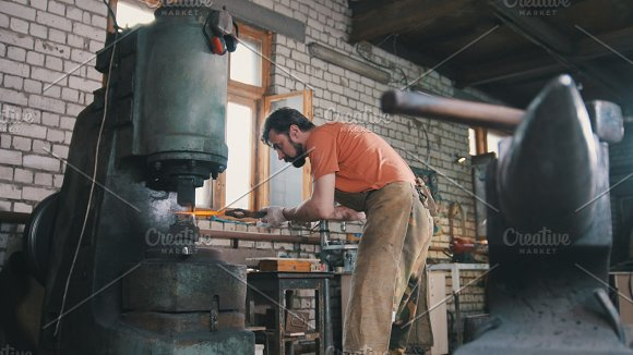 Man blacksmith forges the metal at the mechanical hammer in Graphics