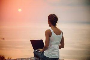 Lady freelancer with laptop on sunset