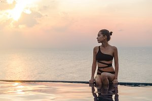 Woman at the infinity pool on sunset