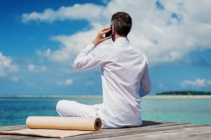 businessman on a wooden talking on a mobile phone