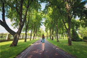 Landscape with woman, trees, green grass, pathway