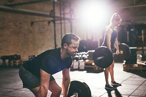 Strong people doing heavy workout with barbells