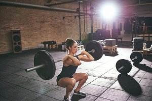 Strong woman squatting with a heavy barbell
