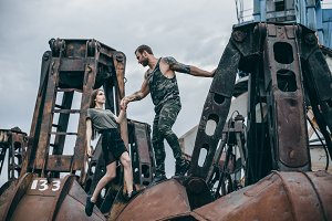 Man with a beard helps a girl to climb on rusty elements