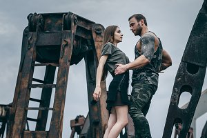 Man and a woman embrace on a rusty pile of metal
