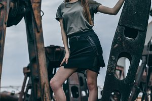 Full length portrait of trendy fashion girl standing on a rusty pile of metal