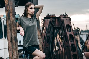 Stylish fashion portrait of trendy casual young model on a metal rusty detail