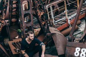 Brutal man with a beard sits on a metal rusty ladle of an abandoned factory