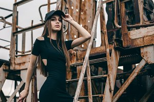 Stylish beautiful girl in a black dress and a cap is standing on a metal rusty staircase
