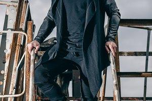 Fashionable man in urban setting in metal rusty ladle