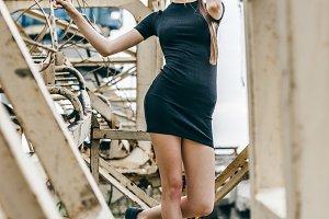 Beautiful young woman wearing fashionable clothes posing on metal railing
