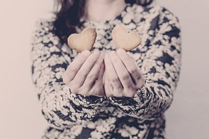 Woman holding two heart cookies