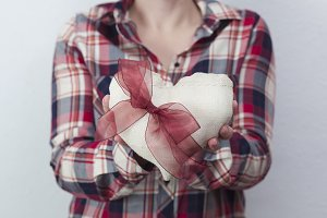 Woman in plaid shirt holding a heart