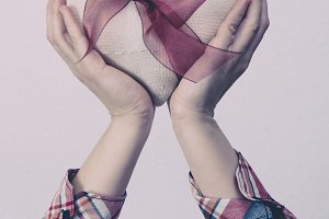 Hands holding a white fabric heart