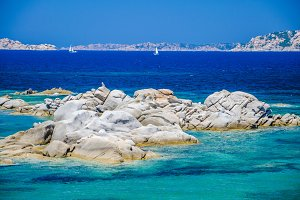 Granite rocks in sea, amazing azure water, white sailboat in background near Porto Pollo, Sardinia, Italy