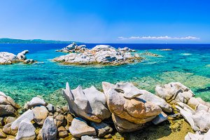 Granite rocks in sea, amazing azure water, white sailboats in background near Porto Pollo, Sardinia, Italy