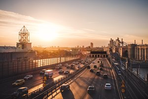 Summer evening cityscape photography of Moscow city with car traffic and amazing sunset above wide road with many cars and modern skyscrapers, Russia outdoor landscape
