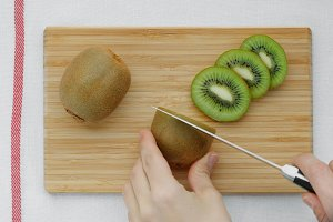 Hands slicing a kiwi on a wooden board