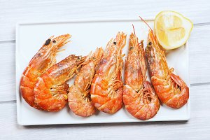 From above shrimps served with lemon on plate on wooden table.