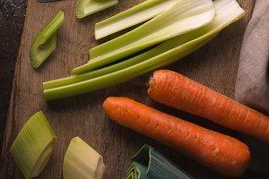 Carrots, celery, leeks on a wooden board
