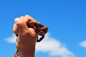 male hand holds a rusty metal chain