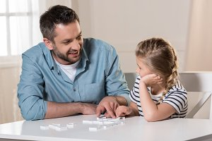 man playing domino with daughter