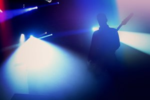 Rock guitarist silhouette on stage.